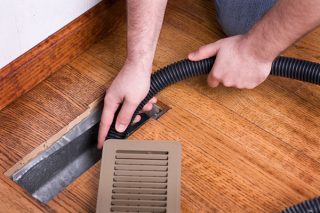 Man cleaning vent air duct